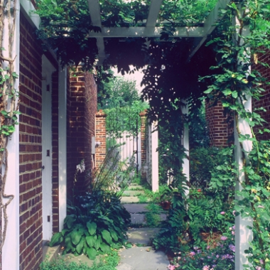 The main garden entrance is announced by climbing Rose and Wisteria arbor leading to the transom-style iron gate. (Arbor by Studio Russo)